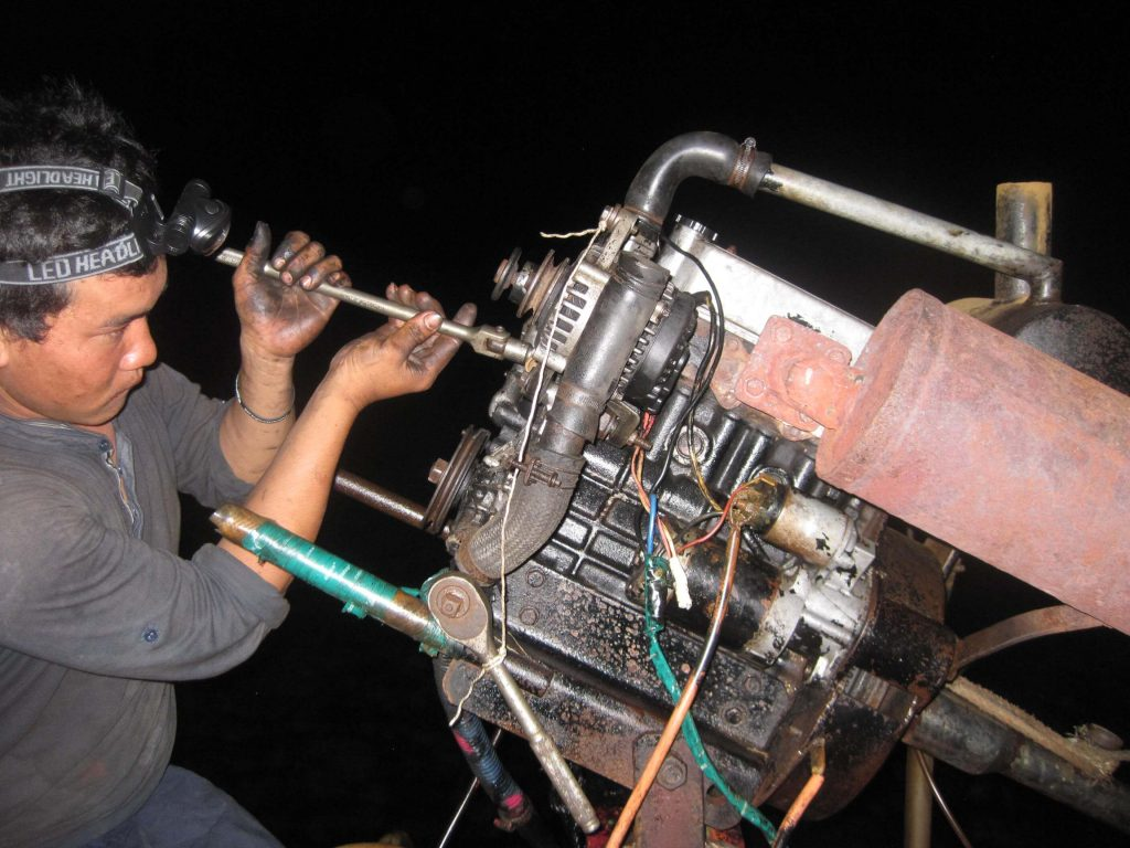 Captain Jiet at working to fix the engine of our boat in Cambodia. ©KettiWilhelm2015
