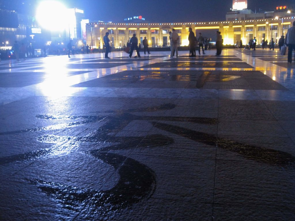 Trying to learn Mandarin from poetry written with a wet mop in a public square in Jinan, China. ©KettiWilhelm2014