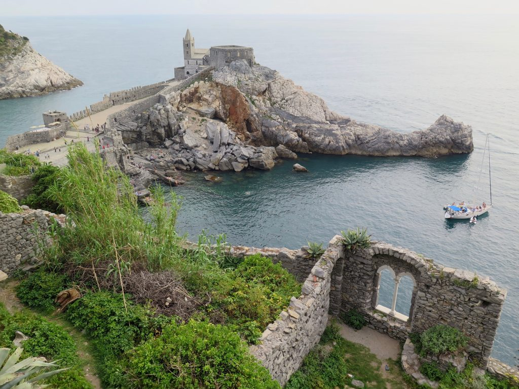 An overlook gazing down on the Ligurian Sea, on Italy's West coast, including an ancient church and a window that's all that remains of what was probably once a beautiful building. (In Cinque Terre, an extremely popular ferragosto destination.) ©KettiWilhelm2018