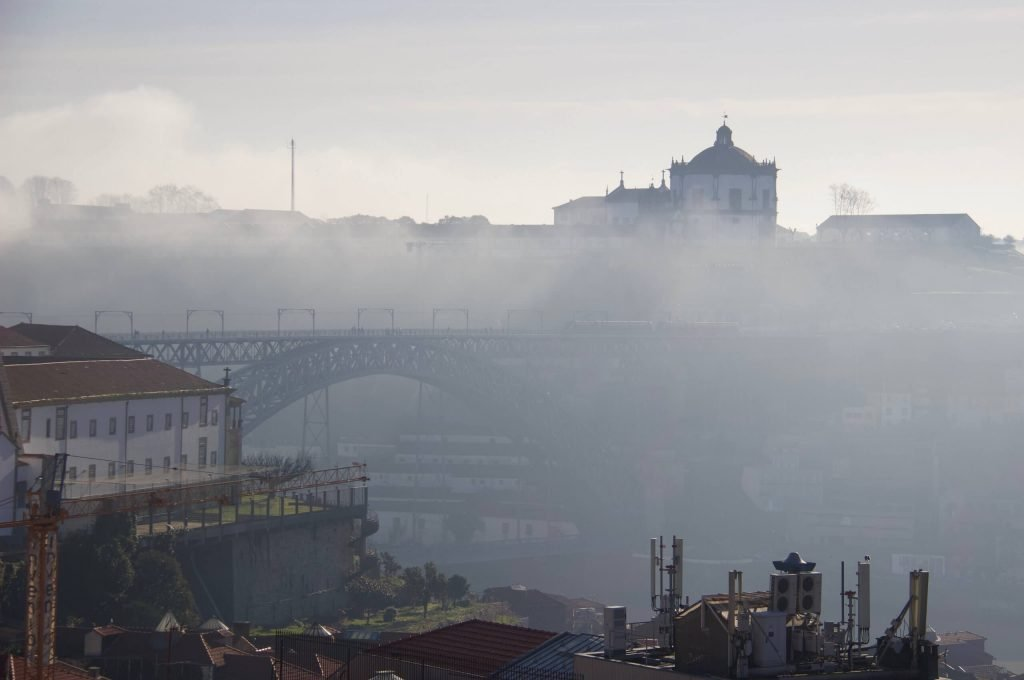Morning fog hanging over the Douro River, with the Dom Luis Bridge and a castle visible in the background. ©KettiWilhelm2020