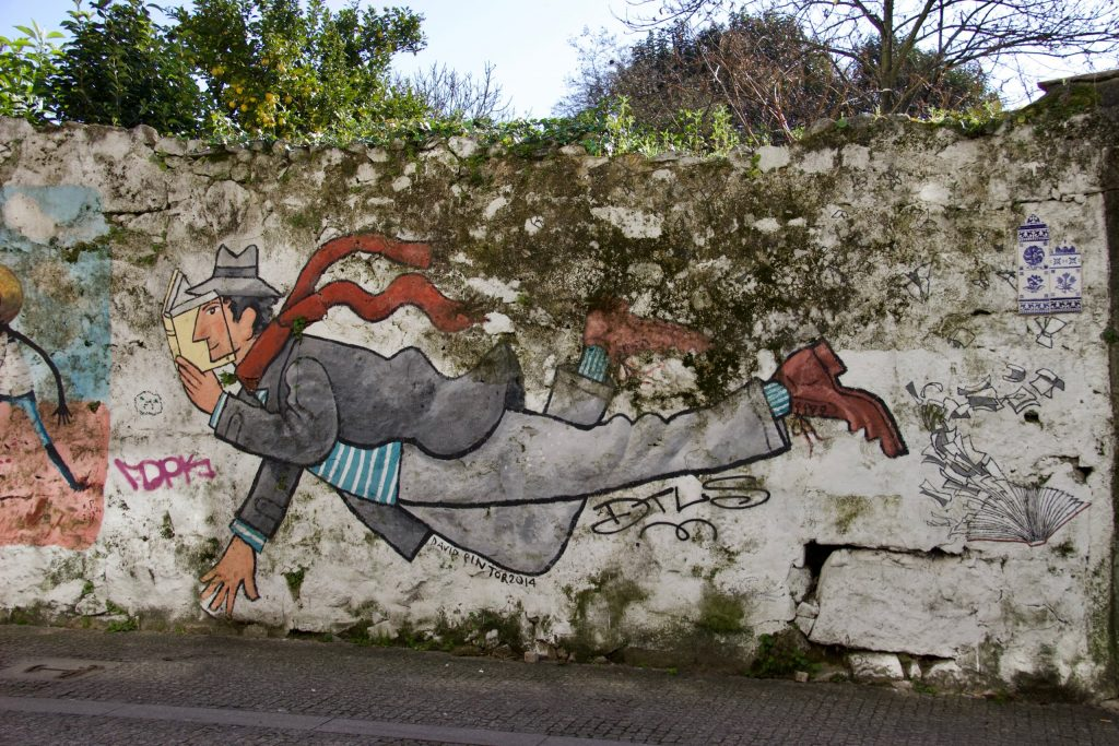A street art painting of a flying man reading a book on Rua de Miguel Bombarda, Porto. ©KettiWilhelm2020