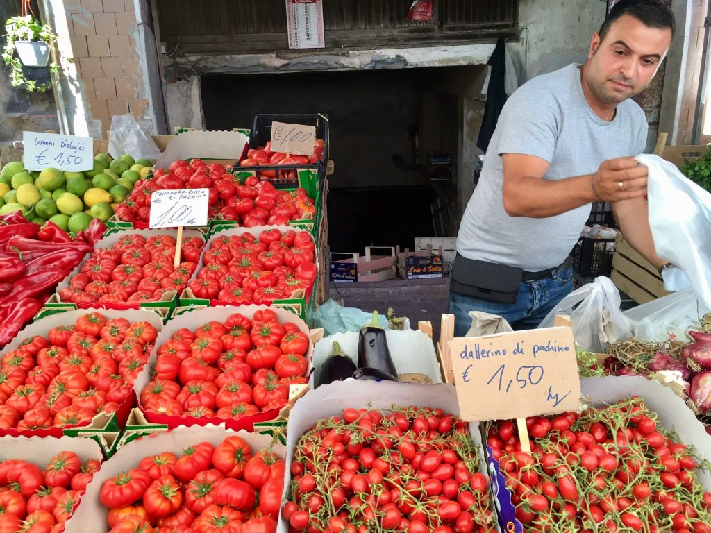 A man selling many varieties of tomatoes at market in Sicily. (Having a diet rich in vegetables is part of how Italians stay thin.) ©KettiWilhelm2017