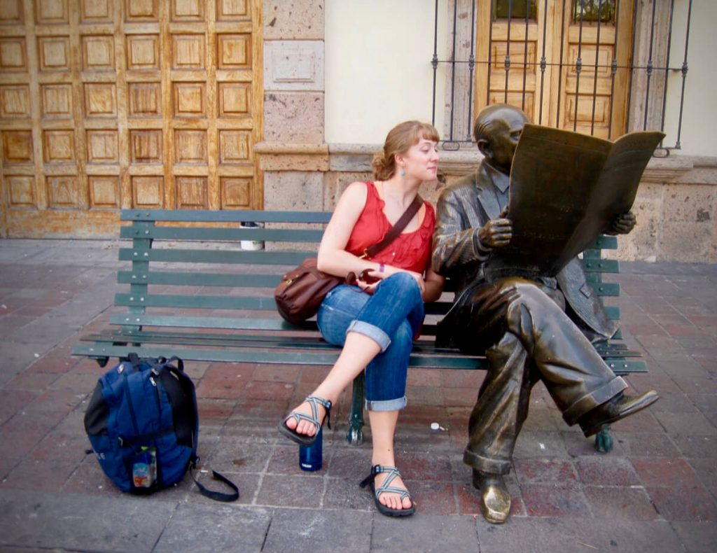 Ketti Wilhelm in Guadalajara, Mexico, sitting next to to a statue of a journalist reading a newspaper. ©KettiWilhelm2013