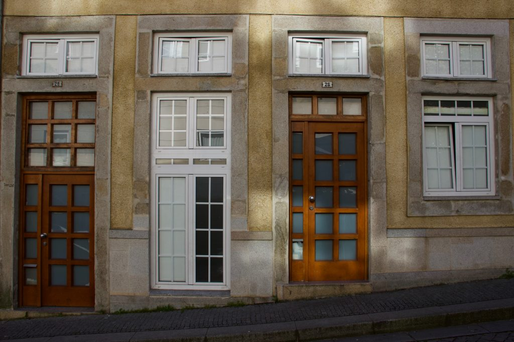 A line of uniform wooden doors and white windows on a street in Porto, Portugal. ©KettiWilhelm2020