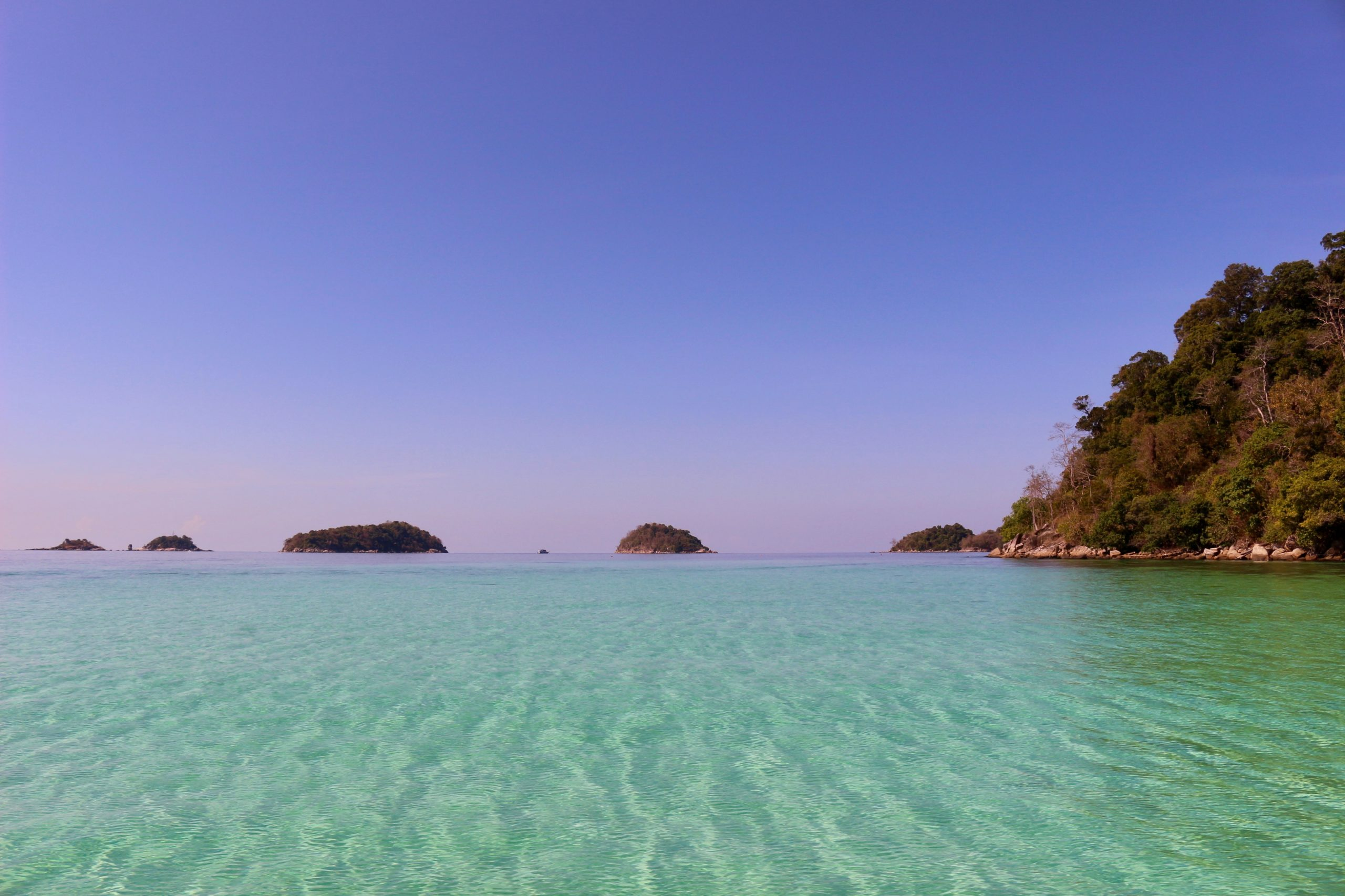 Turquoise waters and a blue sky above a chain of islands in Thailand. ©KettiWilhelm2019