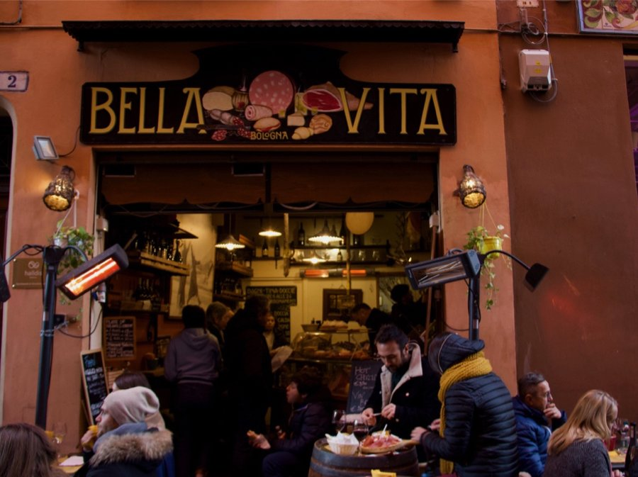 People gathered at a sidewalk restaurant in Bologna, Italy, for aperitivo. ©KettiWilhelm2020
