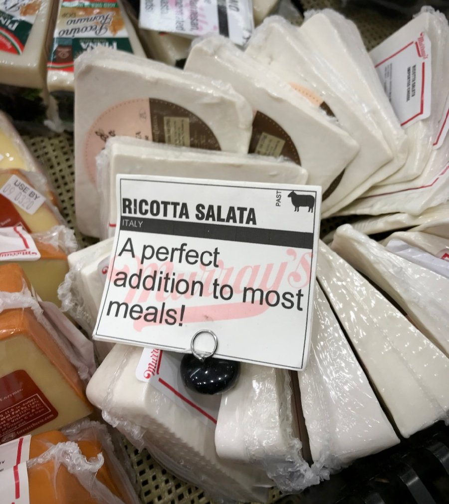 "Ricotta salata cheese in a grocery store display that reads, ""a perfect addition to most meals!"" I love it with lots of pasta recipes. ©KettiWilhelm2020"