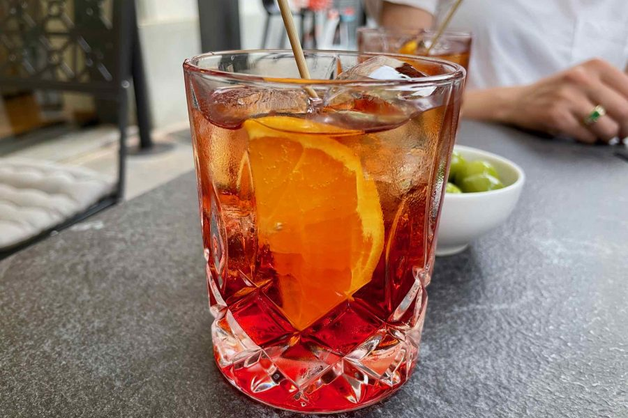 A bright red Americano cocktail – a classic Italian aperitivo drink – with a slice of orange on a table in Milano, Italy. ©KettiWilhelm2021