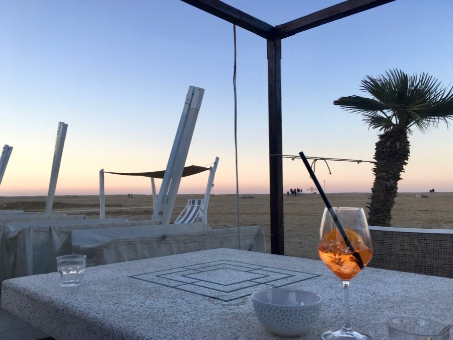 A bright orange Italian cocktail – the famous Aperol Spritz – on a table in front of an empty beach in Rimini, Italy. ©KettiWilhelm
