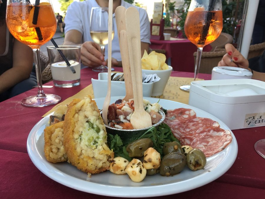 Aperitivo drinks and a typical aperitivo snack platter in Naples, Italy, to share with several people: Arancini, olives, cured meats, and a rice salad. ©KettiWilhelm2020