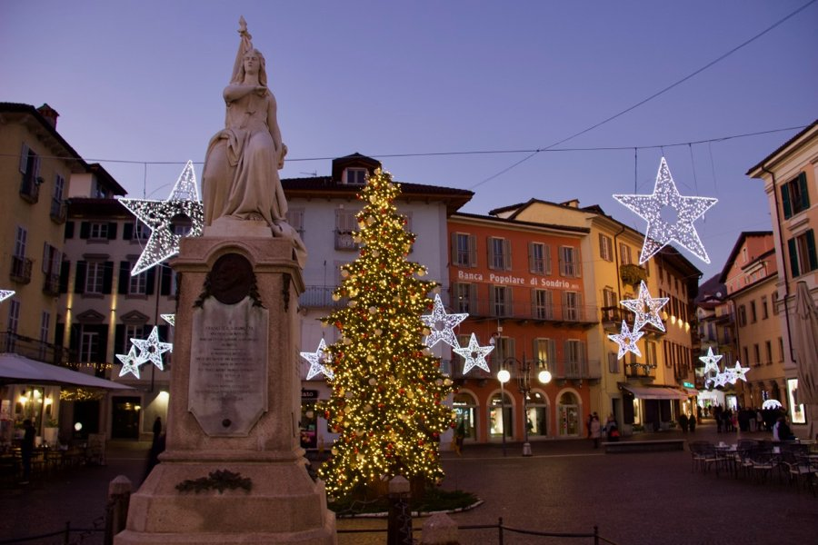 A statue, a Christmas tree, and lots of beautiful lights in a small town plaza at dusk in Italy. ©KettiWilhelm2020