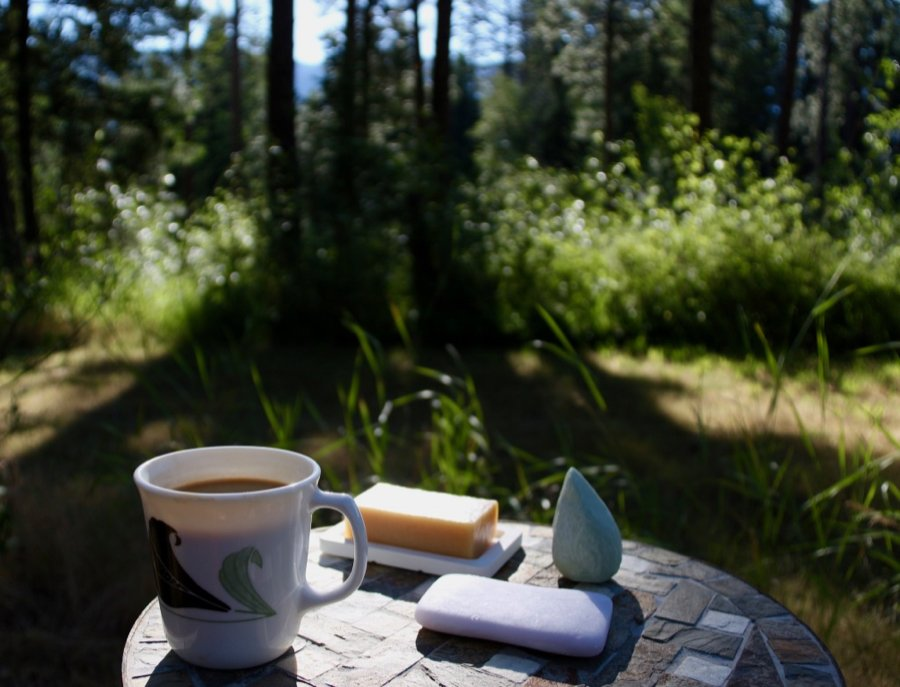 A cup of coffee outside on table next to 3 zero-waste shampoo bars for a photo shoot, with a forest in the background. ©KettiWilhelm
