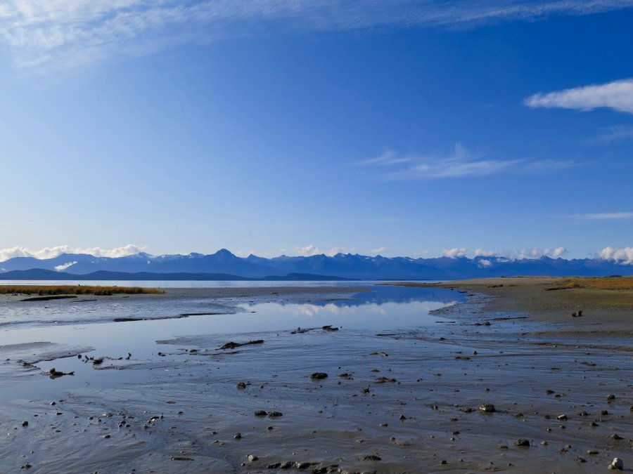 A beach near Juneau, Alaska, covered with a thin layer of water reflecting the mountains behind it on a bluebird day. ©KettiWilhelm2020
