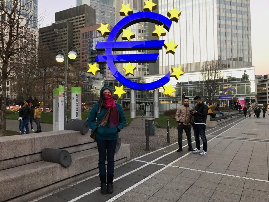 Standing in front of the brightly lit Euro currency sign in Frankfurt, Germany. ©KettiWilhelm2017