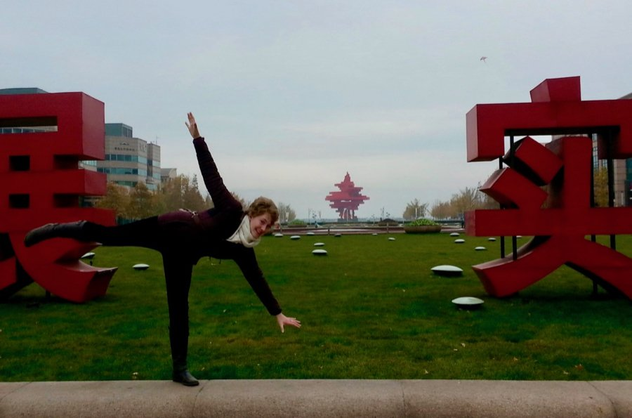 The author, Ketti Wilhelm, doing a cartwheel in front of giant statues of Chinese characters, in Qingdao, China. ©KettiWilhelm2014