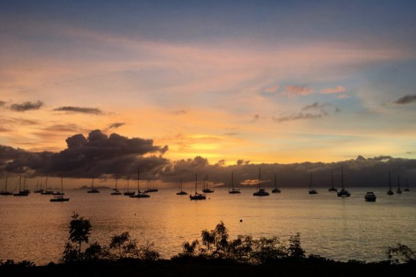 A blue and gold sunset over Caribbean Sea – filled with sailboats – in Guadeloupe. Taken at the end of long work day an international travel guide. ©KettiWilhelm2020