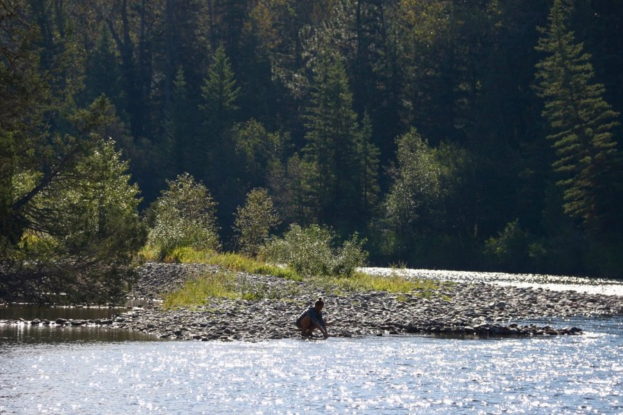 A winding river in Montana, with the blogger in the background, kneeling down, rinsing out her Thinx period underwear (reviewed in this article, with a coupon code) one morning during a camping trip. ©KettiWilhelm2020