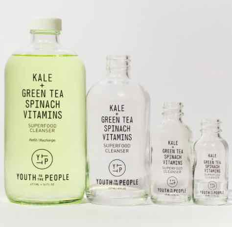 Four glass bottles of Youth To The People Superfood Cleanser (reviewed in this article). The largest bottle, on the left, is full of bright green face wash, while the other smaller refill sizes are empty.