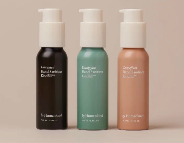 Three aluminum bottles of byHumankind's plastic-free hand sanitizer with reusable pumps. (The refillable bottles are black, teal, and mauve on a light background.)