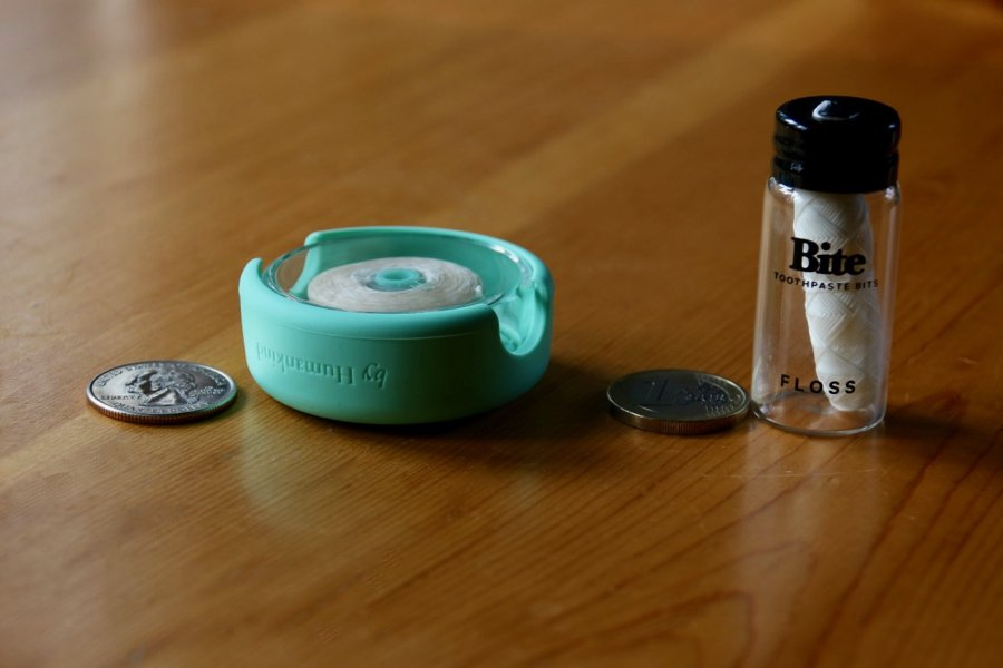 Two plastic-free dental floss options – byHumankind in a green, silicone and glass reusable container, and Bite, in a refillable glass jar – on a wooden table next to a quarter and a Euro for size comparison. ©KettiWilhelm2020
