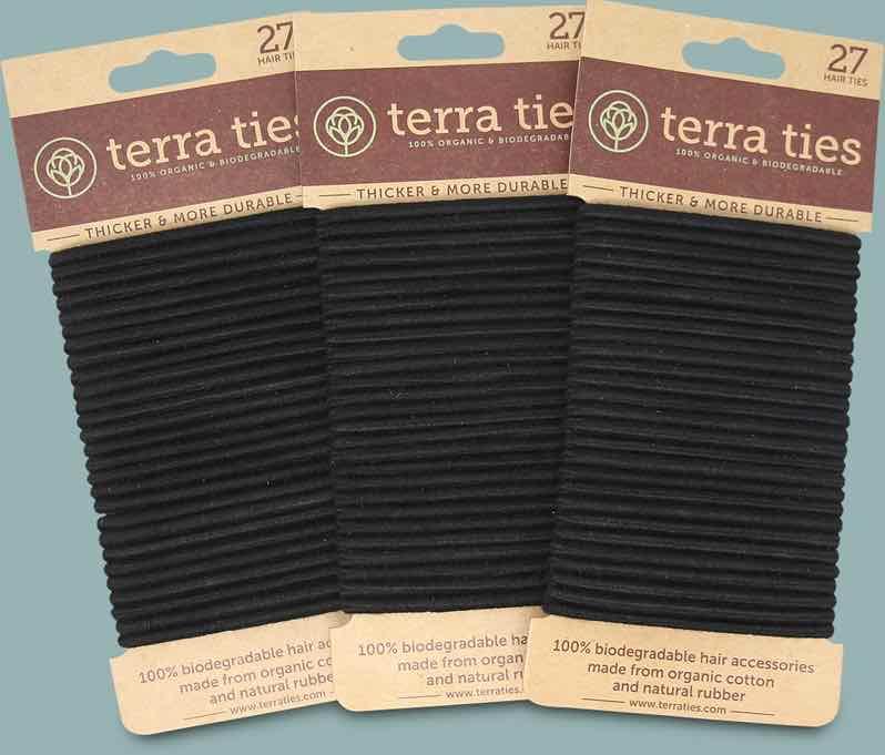Three packs of simple, black, plastic-free, biodegradable and organic hair ties from Terra Ties, and cardboard packaging.