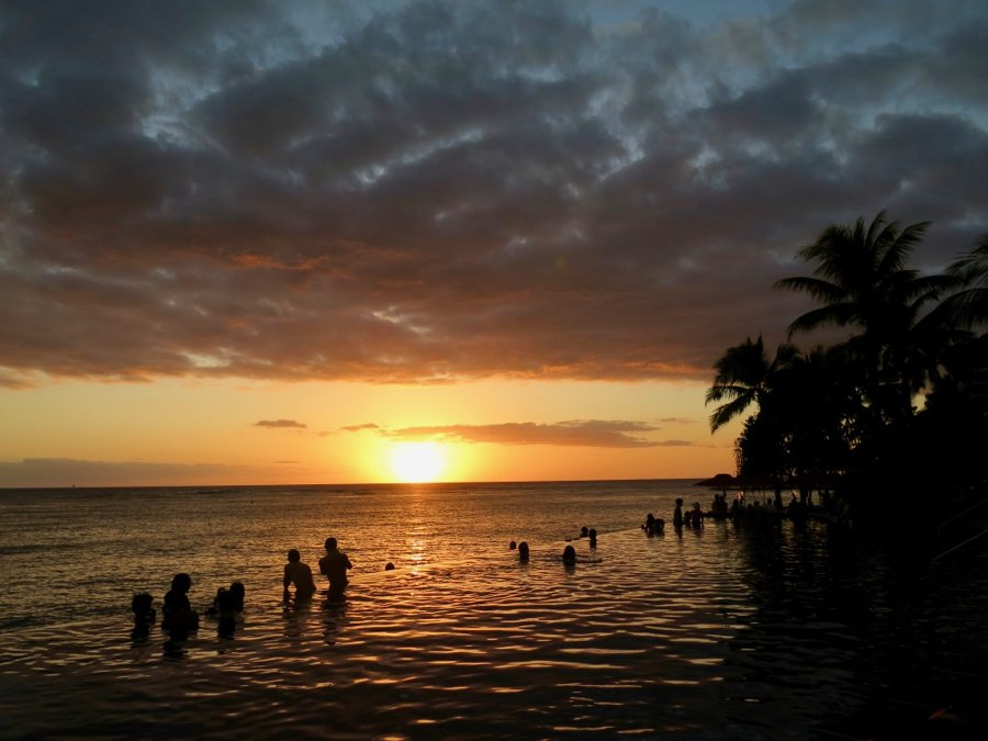 An orange sunset from an infinity pool on Oahu, Hawaii. Two people snap photos by the edge of the pool – it's clearly from pre-COVID travel days. ©KettiWilhelm2020