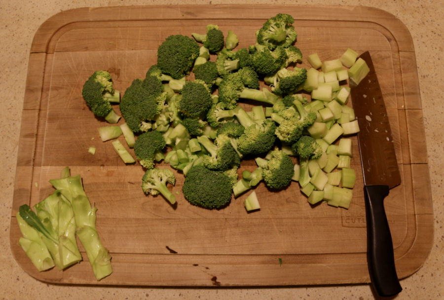 Chopped broccoli, including the peeled stems, on a wooden cutting board, prepped for to be boiled for Pasta with Broccoli. ©KettiWilhelm2021