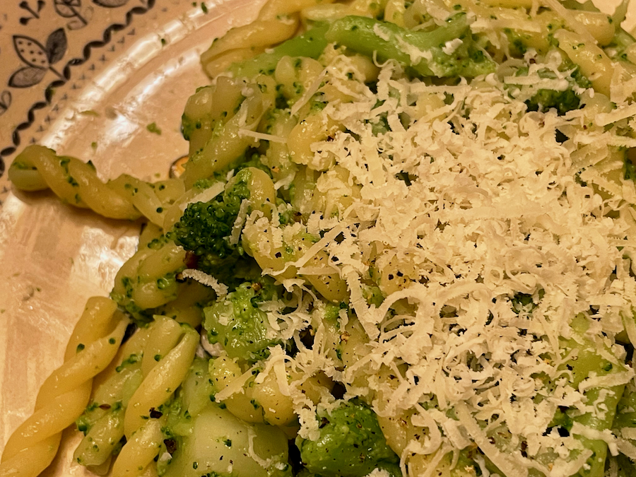 A very close-up shot of a plate of fusilli pasta with broccoli, topped with Parmigiano Reggiano cheese. An authentic Italian recipe. © KettiWilhelm2021
