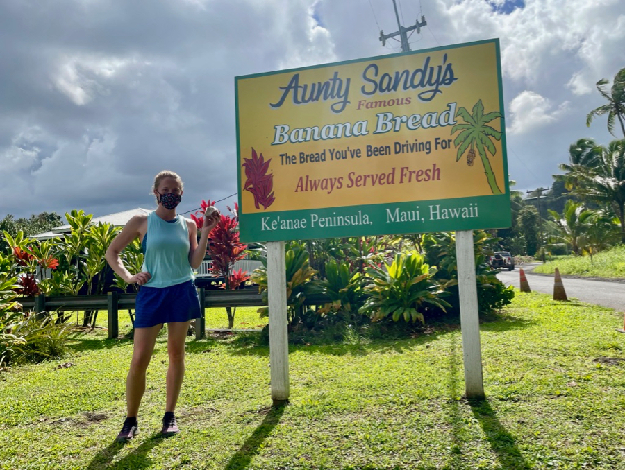 The author on Maui, wearing a mask, next to a sign for Aunty Sandy's banana bread, under stormy skies. ©KettiWIlhelm2021