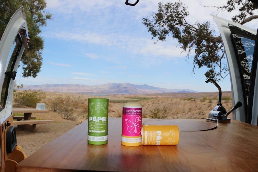 Two tubes of PAPR deodorant (plastic-free, in cardboard packaging) on a wood table with a sink inside a camper van, with the Nevada desert behind them. ©KettiWilhelm2021