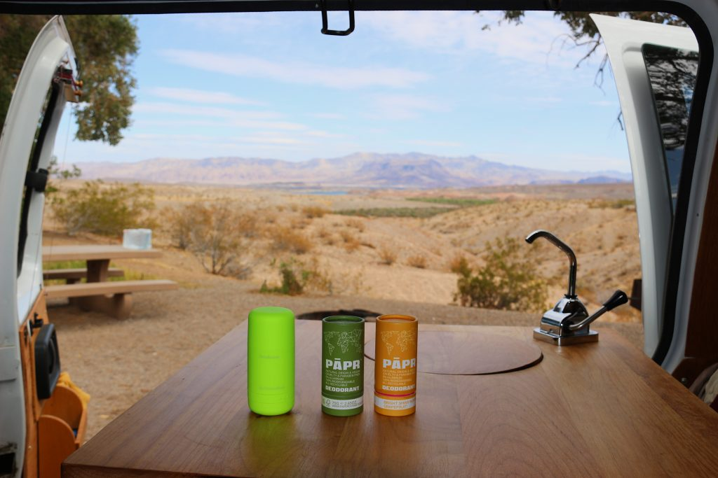 Three tubes of zero-waste deodorant (by the eco-friendly brands byHumankind and PAPR deodorant) on a wood table with a sink inside a camper van, with the Nevada desert behind them. ©KettiWilhelm2021