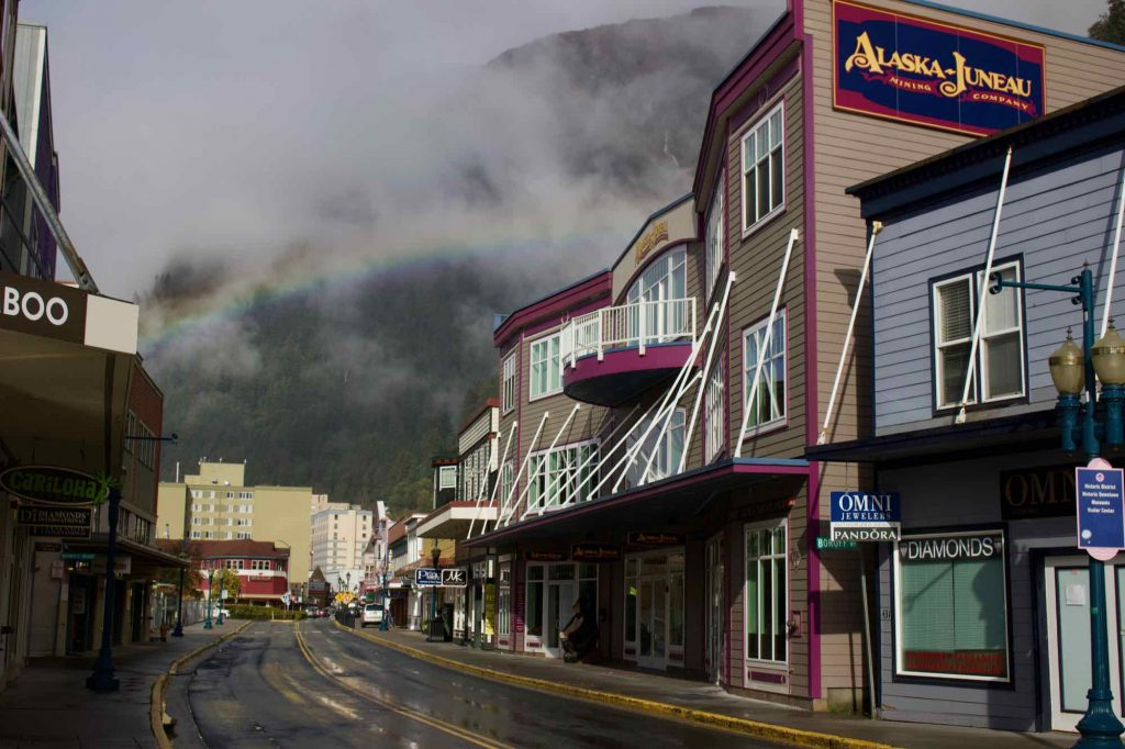 A rainbow forms in downtown Juneau, over a narrow, curved street filled with touristic shops. ©KettiWilhelm2021