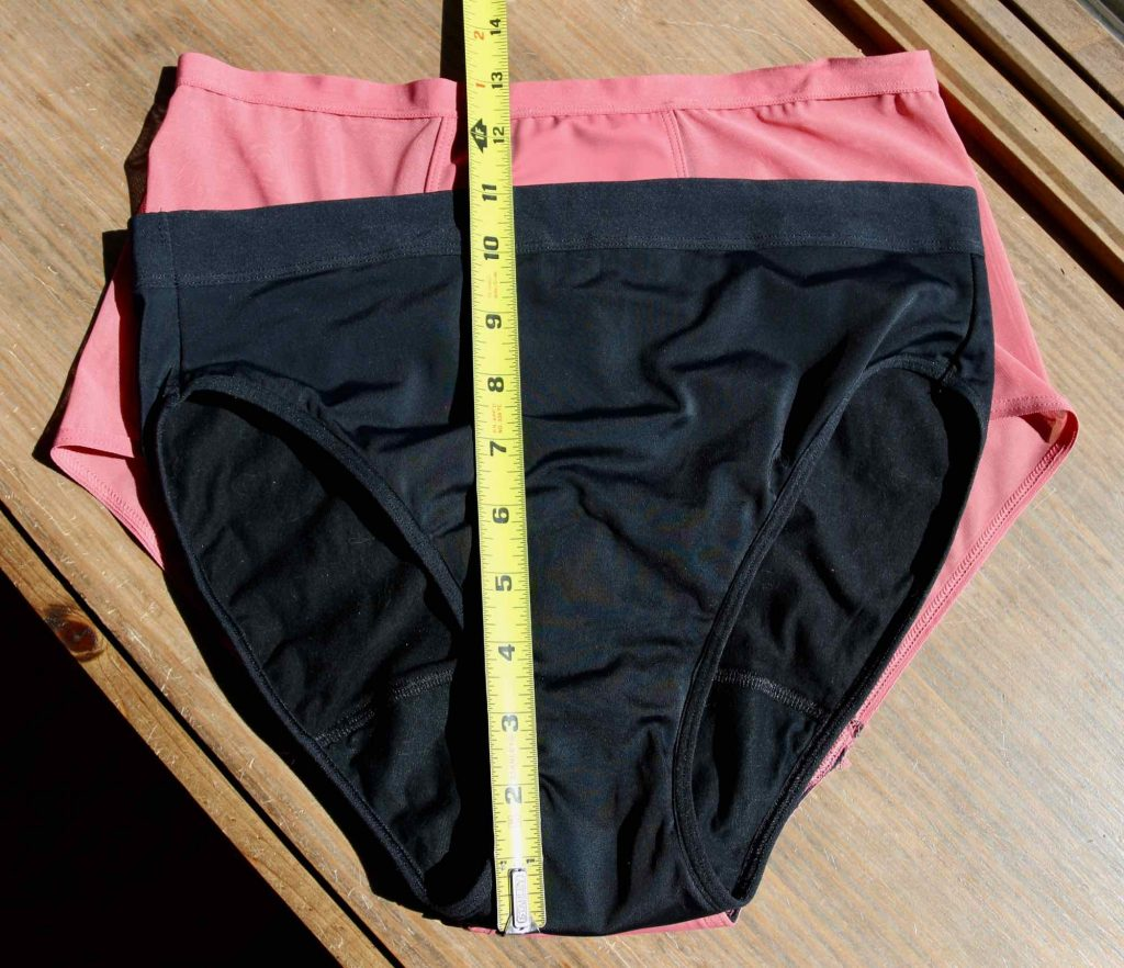 A comparison of Thinx's Hi Waist style versus their French Cut: The French Cut is laid on top of the Hi Waist with a tape measure showing the difference in the rise between the two similar styles. ©KettiWilhelm2021