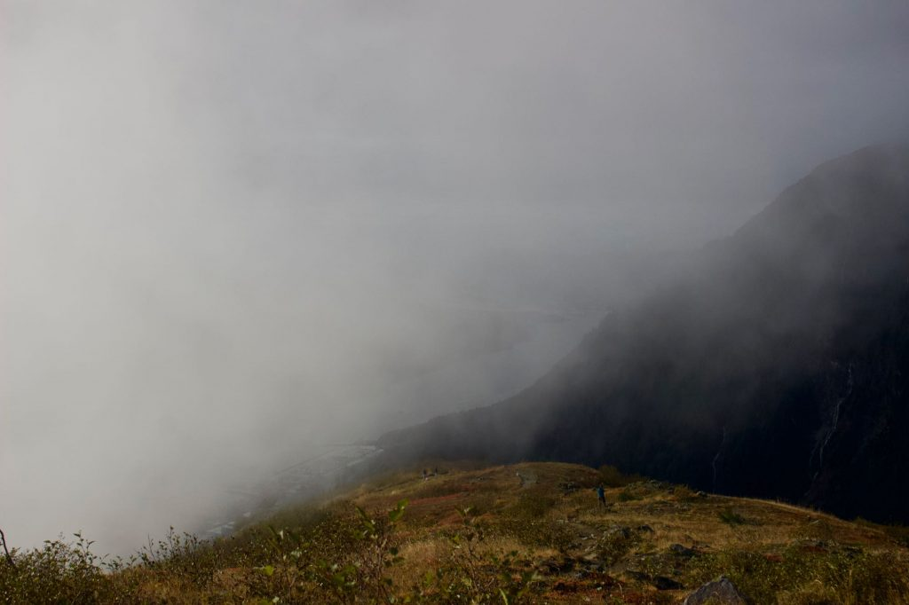 Thick fog rolling up the steep front of Mt. Roberts, obscuring the view of the city of Juneau below. ©KettiWilhelm2021