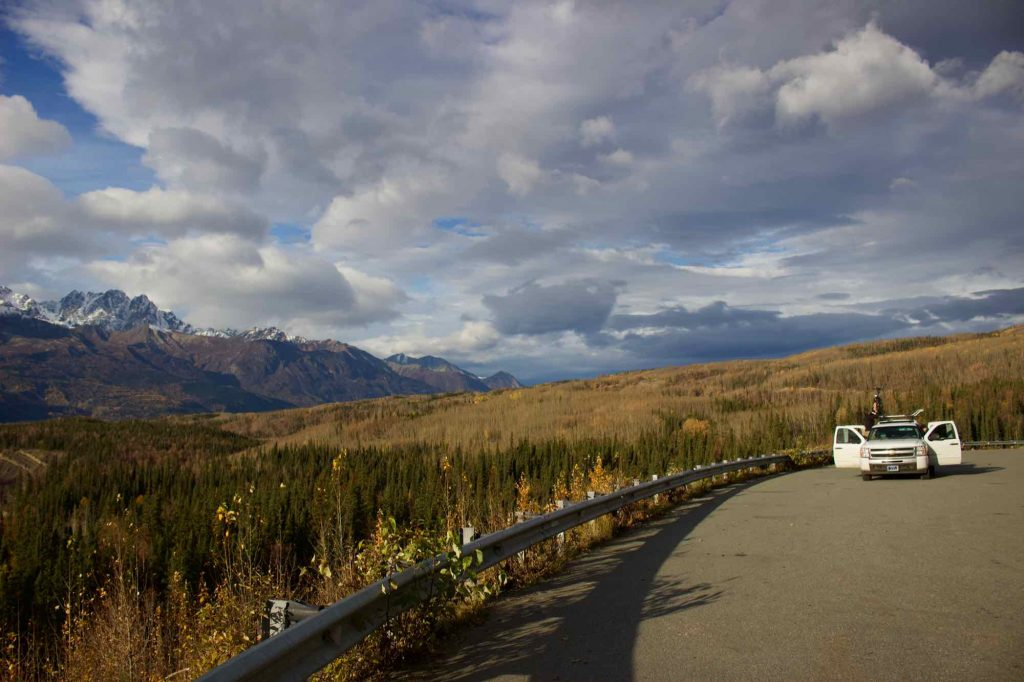 The white pickup truck that the author used for a road trip around Alaska, parked by a guardrail, next to an expansive view of a wide river valley and mountains. ©KettiWilhelm2021