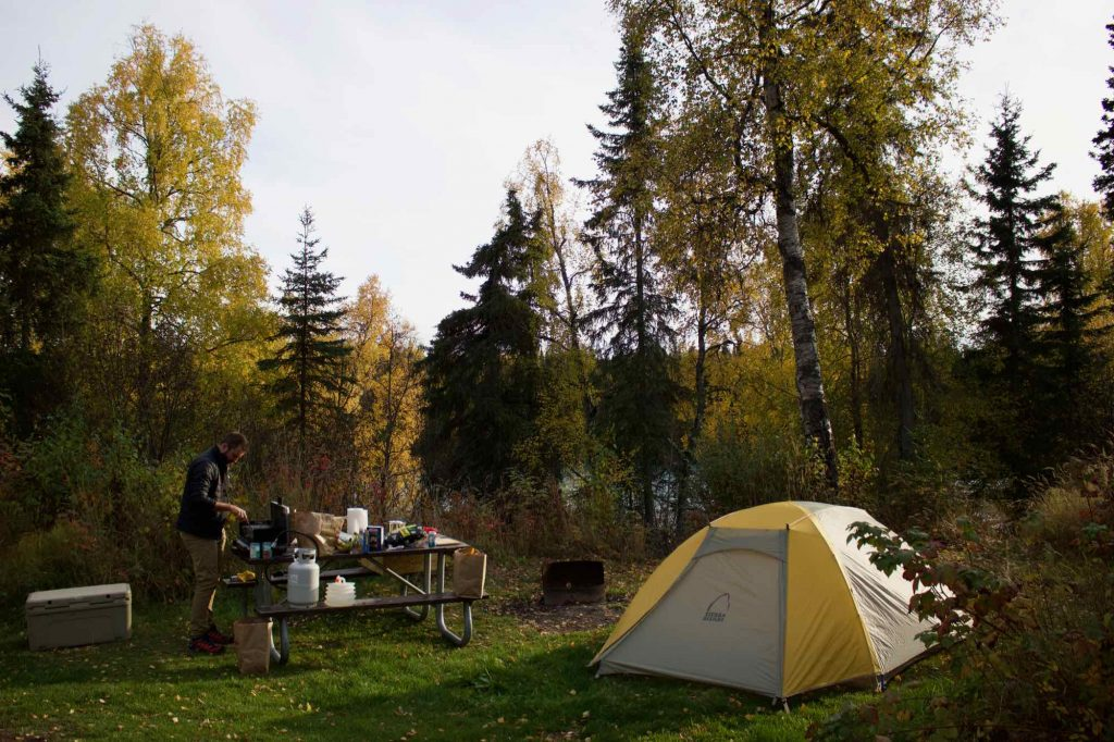 On the right, the yellow and white tent that the blogger slept in while traveling in Alaska, and her husband cooking dinner at a camp stove on a picnic table on the left, with yellow-leafed autumn trees behind. ©KettiWilhelm2021