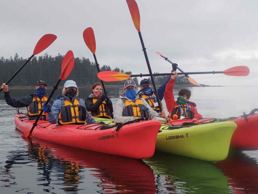 UnCruise guests in Alaska in kayaks wearing masking, lifting their paddles in the air. ©UnCruise