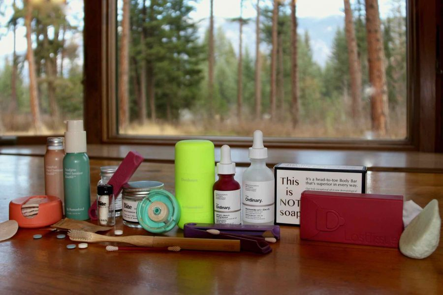My zero-waste toiletry routine (including plastic-free deodorant, hand sanitizer, floss, and much more) sitting on a wooden table with a natural scene (trees and plants) in the background outside. ©KettiWilhelm2021