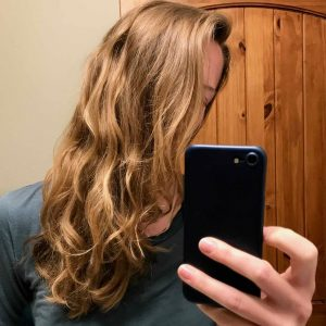 A selfie of my wavy, sandy blonde hair after using Earthling shampoo and conditioner bars for a month (without even brushing it, as I was traveling a van for that month!). ©KettiWilhelm2021