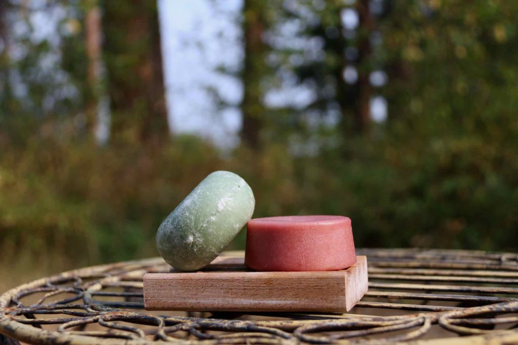 Two Earthling Co. bars – a green shampoo bar resting on top of a pink conditioner bar – in a natural setting, outside with trees in the background. ©KettiWilhelm2021