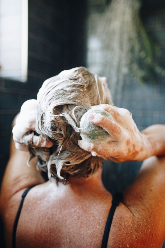 The head and shoulders of a white woman with blond hair in a shower lathering up her hair with an Earthling Co. shampoo bar – the brand's rich lather is one reason I think they're some of the best shampoo bars in this review.