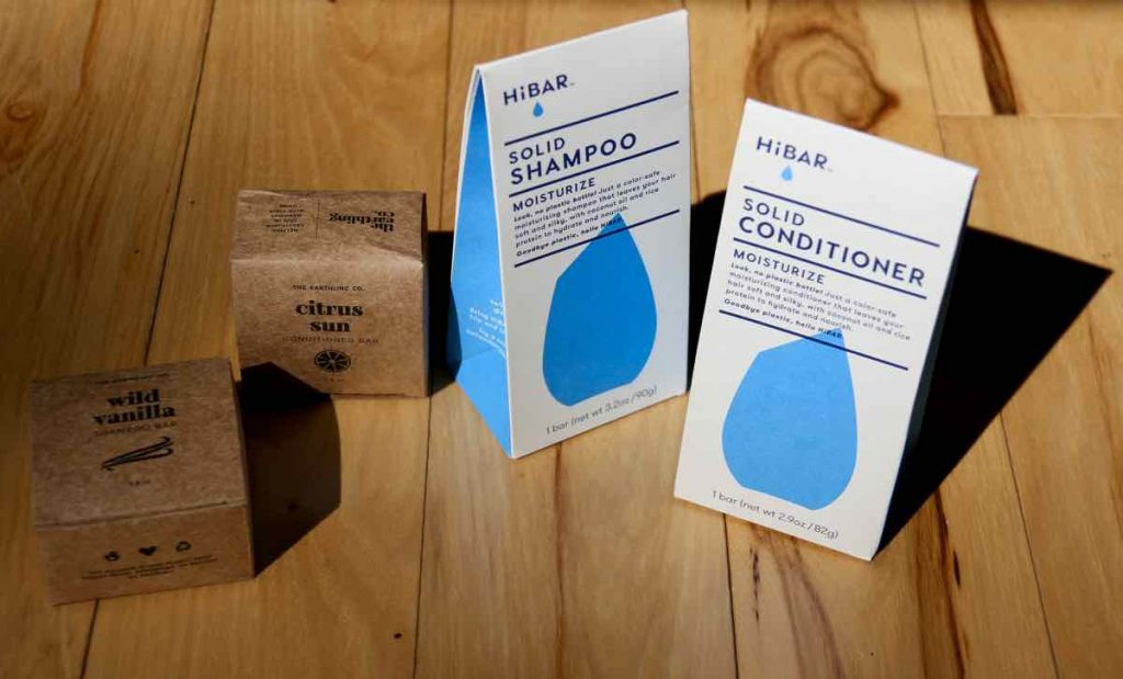 Displayed on a light-colored wooden surface are the compostable, recycled and recyclable paper packaging from Earthling Co. shampoo and conditioner bars (on the left) and HiBAR shampoo and conditioner bars (on the right). ©KettiWilhelm2021