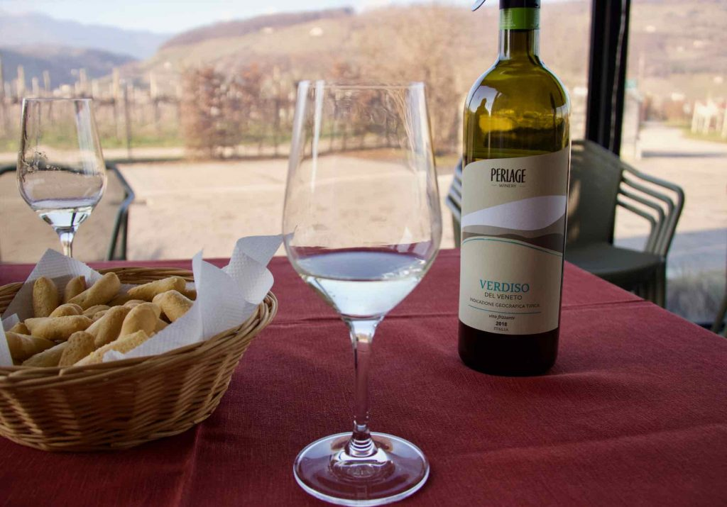 A glass of organic Prosecco at the Perlage Winery in Valdobbiadene, Italy – an easy choice to make a wine tasting trip more sustainable. A bottle of wine and basket of crackers are in the background. ©KettiWilhelm2021
