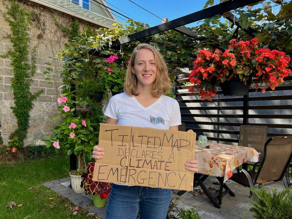 """The author, sustainable travel blogger Ketti Wilhelm, holds a cardboard sign saying """"Tilted Map declares a climate emergency,"""" joining Tourism Declares. ©KettiWilhelm2021"""