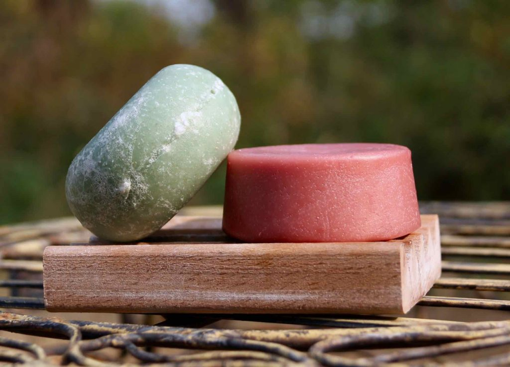 Green and pink shampoo and conditioner bars outdoors on a soap dish, with a green, natural background. Solid toiletries are an easy part of a sustainable travel routine. ©KettiWilhelm2021