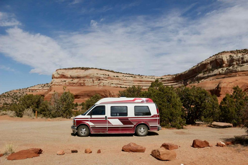The homemade van conversion the author built, parked at a campground in front of a red rock landscape in Utah. Converting an older van is a sustainable travel choice in that it reuses something old, instead of starting from scratch. ©KettiWilhelm2021